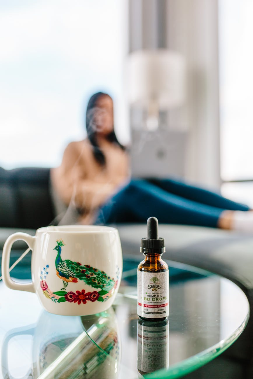 bottle of cbd drops next to cup with hot drink