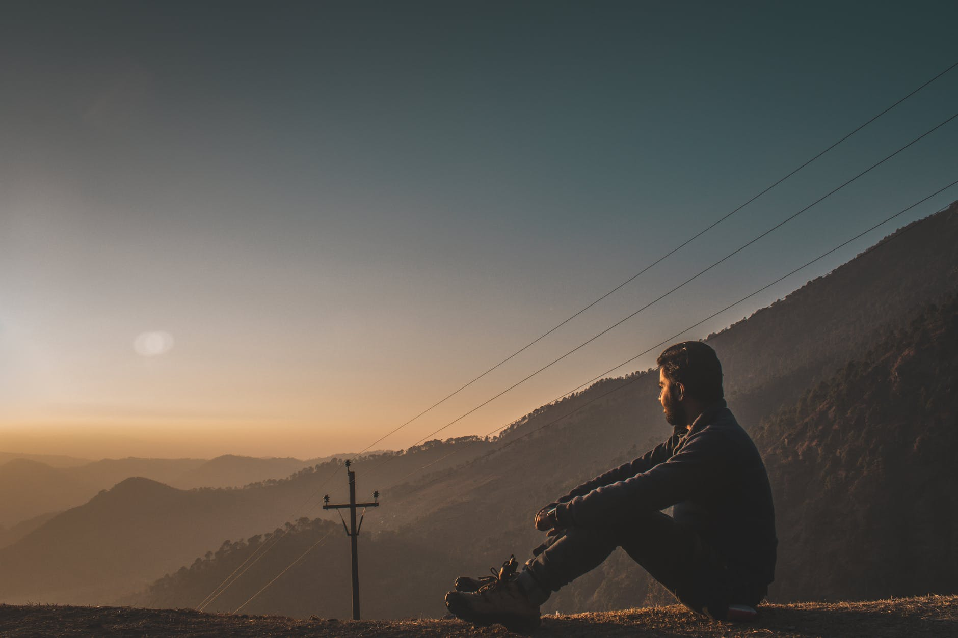 man sitting on hill facing sunrise