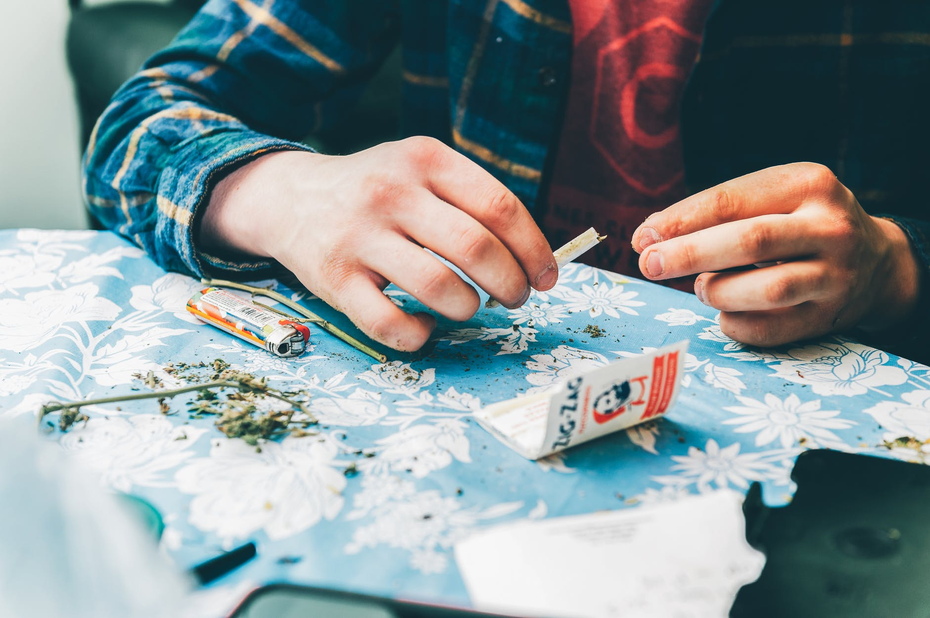 person rolling a paper with weed
