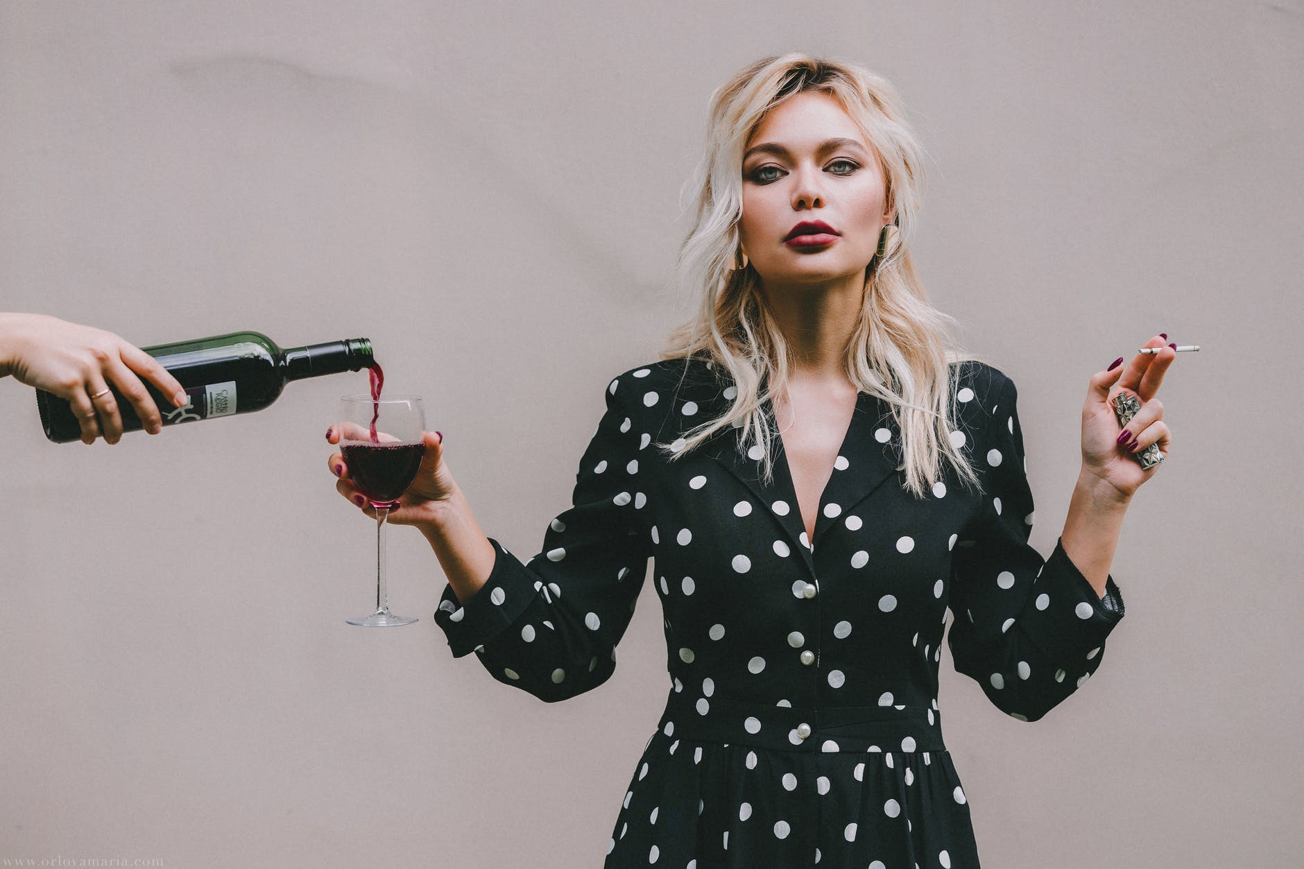 confident woman standing with wineglass and cigarette